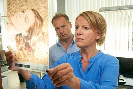 Was genau ist passiert?Jürgen Simmel (Hinnerk Schönemann) und Marie Brand (Mariele Millowitsch) begutachten ein Foto der Toten Annika Herforth. Foto: Guido Engels/ZDF/dpa