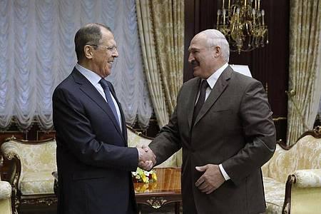 ARCHIV - Sergej Lawrow (l), Außenminister von Russland, schüttelt die Hand von Alexander Lukaschenko, Präsident von Belarus. Foto: ---/Russian Foreign Ministry/AP Press Service/dpa