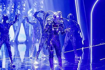 Wer mag in der Maske des Roboters stecken?. Foto: Rolf Vennenbernd/dpa
