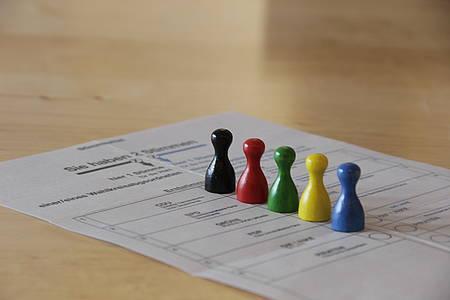 Bunte Spielfiguren auf einem Wahlzettel