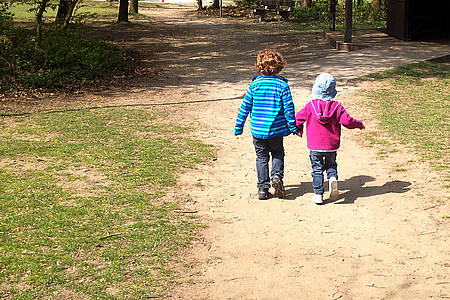 Zwei Kinder Hand in Hand beim Spazierengehen