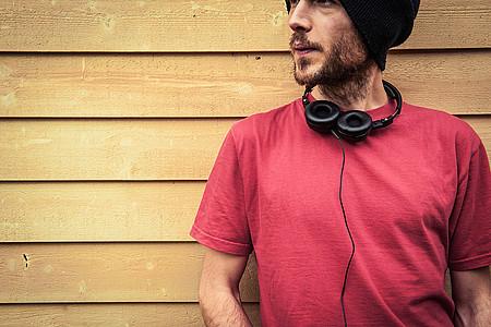 Mann mit rotem T-Shirt und Kopfhörern