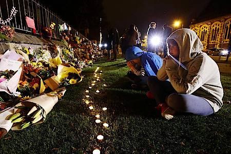 Menschen trauern vor Kerzen und Blumen, die in Gedenken an die Opfer der Anschläge auf zwei Moscheen in Christchurch, Neuseeland niedergelegt wurden. Foto: ---/kyodo/dpa