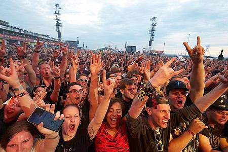 Rockfans jubeln vor der Hauptbühne des Open-Air-Festivals «Rock am Ring». Foto: Thomas Frey/dpa