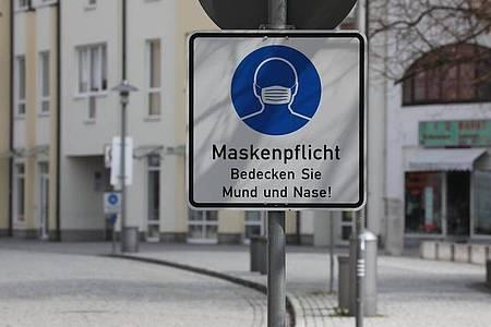 Ein Hinweisschild zur Maskenpflicht steht an der Fußgängerzone. Foto: Bodo Schackow/dpa-Zentralbild/dpa