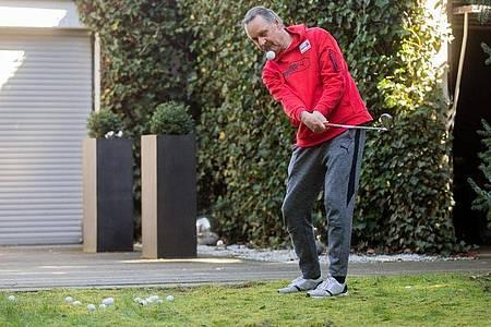 Peter Neururer übt in seinem Garten Golf. Foto: Rolf Vennenbernd/dpa