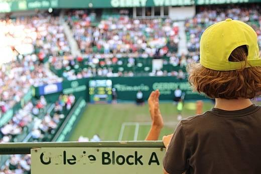 Kind applaudiert auf einem Tennisplatz
