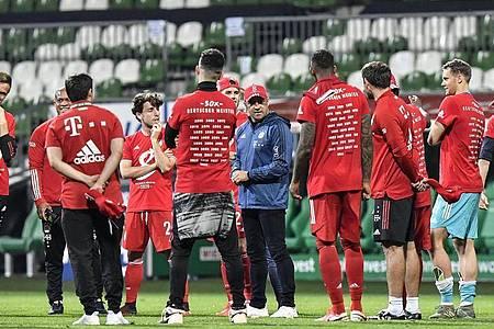 Bayern-Coach Hansi Flick (M) hält in Bremen seine erste Ansprache als Meistertrainer. Foto: Martin Meissner/AP-Pool/dpa