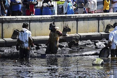 Arbeiter versuchen ein Küstengebiet von einem Ölteppich zu reinigen. Foto: Ajai Daby/XinHua/dpa