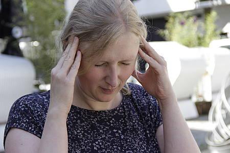 Frau fasst sich mit den Händen an den Kopf