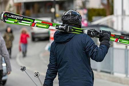 Ein Skifahrer geht mit geschulterten Skiern auf einer Straße im Skiort Ischgl. Foto: Jakob Gruber/APA/dpa