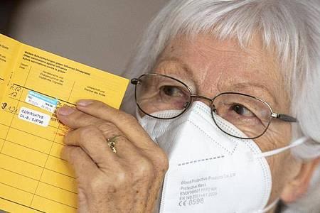 Seniorin Ursula Neuberger hält ihren Impfpass, in dem eine Grippe-Impfung (oben) und ihre erste Corona-Impfung vermerkt sind. Foto: Stefan Puchner/dpa