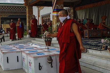 Mönche des Klosters von Paro führen ein Ritual durch, nachdem 500.000 Dosen des von den USA gespendeten Corona-Impfstoffs von Moderna am internationalen Flughafen von Paro ankamen. Foto: Uncredited/UNICEF/AP/dpa
