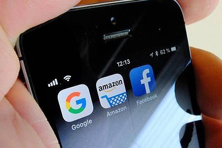 Logos für Apps von Google, Amazon und Facebook auf dem Display eines Smartphones. - Seit Jahren werden in der Politik vielfach schärfere Steuerregelungen für große Digitalkonzerne gefordert. Foto: Stefan Jaitner/dpa