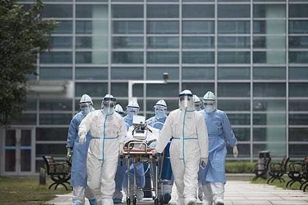 Medizinisches Personal mit einem Covid-19-Patienten im chinesischen Wuhan. Einer Studie zufolge entwickelten sich die Corona-Hotspots in Regionen mit ähnlichen Klimafaktoren. Foto: Fei Maohua/XinHua/dpa