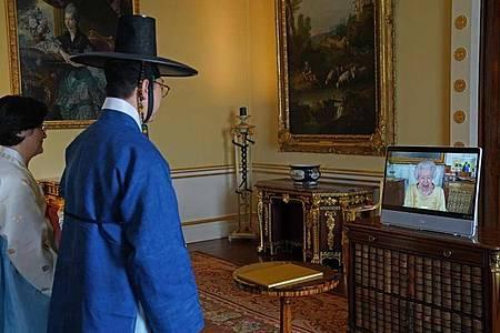 Der südkoreansiche Botschafter Gunn Kim (m.) bei der virtuellen Audienz im Buckingham Palace mit Königin Elizabeth. Foto: Victoria Jones/PA Wire/dpa