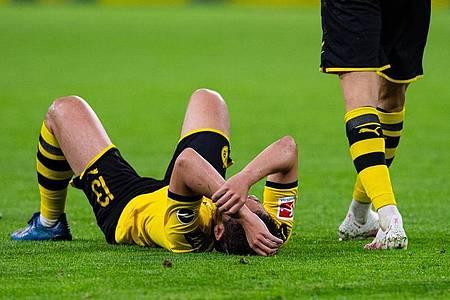 BVB-Spieler Raphael Guerreiro liegt auf dem Rasen. Foto: Guido Kirchner/dpa-pool/dpa
