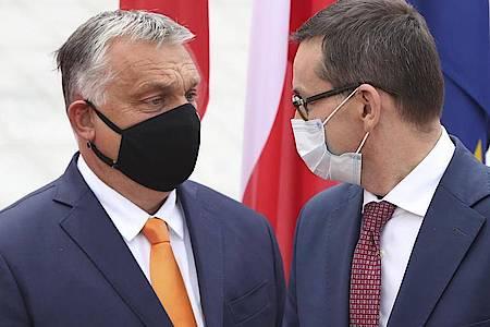 Polens Premierminister Mateusz Morawiecki begrüßt seinen ungarischen Amtskollegen Viktor Orban. Eine Mehrheit der EU-Staaten hat ungeachtet von Drohungen aus Ungarn und Polen ein Verfahren zur Bestrafung von Verstößen gegen die Rechtsstaatlichkeit innerha