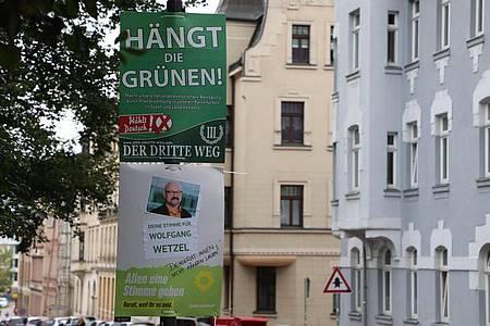 """Ein umstrittenes Wahlplakat der Splitterpartei """"III Weg"""" hängt über einem Plakat der grünen. Foto: Bodo Schackow/dpa-Zentralbild/dpa"""