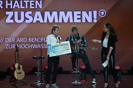 Der deutsche Sänger Peter Maffay (l) überreicht Moderatorin Sarah von Neuburg auf der Bühne der ARD-Benefizgala einen Spendenscheck. Foto: Hendrik Schmidt/dpa-Zentralbild/dpa