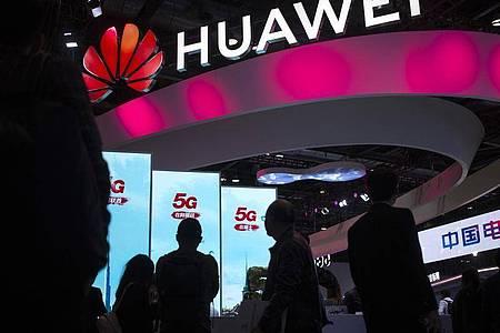 Besucher gehen an einem Display für 5G-Dienste des chinesischen Technologieunternehmens Huawei auf der PT Expo in Peking vorbei. Foto: Mark Schiefelbein/AP/dpa