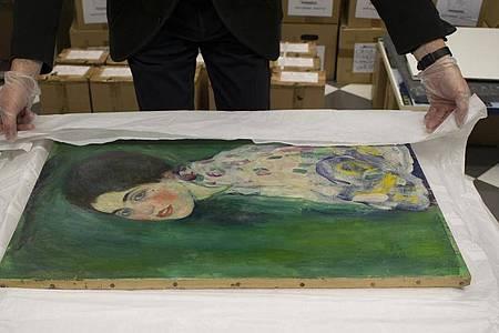 """Ein Mitarbeiter der Galerie Ricci Oddi packt das wiederentdeckte Klimt-Gemälde """"Bildnis einer Frau"""" aus. Foto: -/Galerie Ricci Oddi /dpa"""
