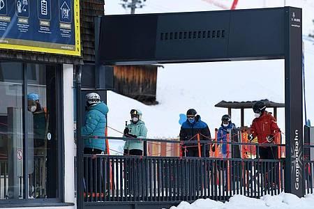 Wintersportler stehen in Tirol mit Mund-Nasen-Schutz an einem Skilift Schlange. Foto: Helmut Fohringer/APA/dpa