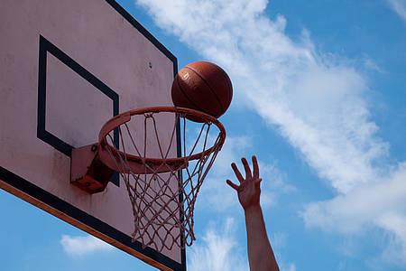 Hand wirft Ball in Basketballkorb