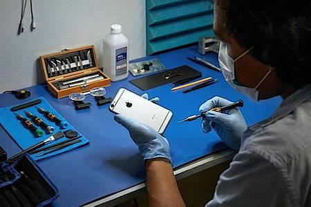 Ein Service-Techniker arbeitet an einem iPhone. Foto: Apple/dpa