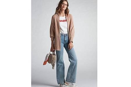 Auch ein Element der Siebziger: Die Flare Jeans, eine Hose mit weit ausgestelltem Bein. Hier ein Beispiel von Oui (Strickjacke ca. 150 Euro, T-Shirt ca. 30 Euro, Denim ca. 120 Euro). Foto: Oui/dpa-tmn