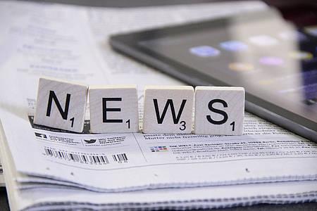 """Scrabble-Buchstaben """"News"""" auf einer Zeitung"""