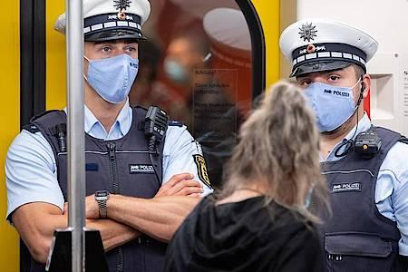 Polizeibeamte kontrollieren in einer Stuttgarter U-Bahn die Einhaltung der Maskenpflicht. Foto: Sebastian Gollnow/dpa