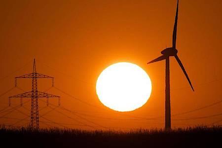 Die Silhouette eines Windrades (r) zeichnet sich vor der aufgehenden Sonne ab. Foto: Julian Stratenschulte/dpa