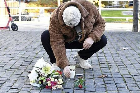 Ein Mann legt am Tatort Blumen und eine Kerze für den Musiker Einár nieder. Foto: Henrik Montgomery/TT NEWS AGENCY/dpa