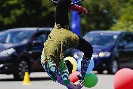 Familien passieren bei der Fahrt durch das «Zirkusland» verschiedene Attraktionen mit Clowns, Jongleuren, Einradfahrern, Seiltänzern und Trapez-Künstlern. Foto: Uwe Anspach/dpa