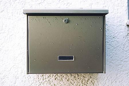 silbener Briefkasten an einer Wand