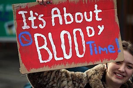 """Eine Frau in Edinburgh hält bei einer Kundgebung ein Schild mit der Aufschrift """"It`s about bloody time!"""" (dt. Es ist verdammt noch mal an der Zeit) hoch. Foto: Andrew Milligan/PA Wire/dpa"""