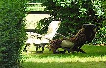 Hölzerne Liegestühle mit Fellen in sonnig, grünem Garten
