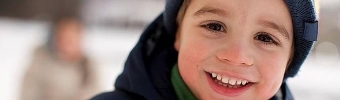 Junge mit Mütze lacht in die Kamera