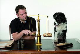 Martin Rütter und ein Hund sitzen am Schreibtisch