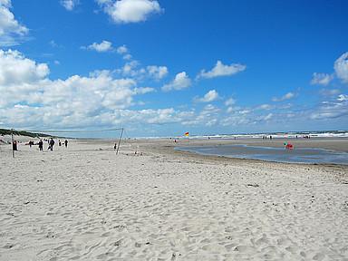 Strand mit Beachvolleyballfeld, blauer Himmel