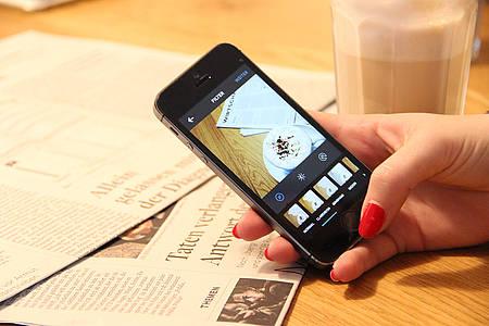Frau mit roten Fingernägeln tippt auf dem Smartphone Instagram-Beitrag ein