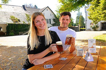 Frau und Bier stoßen im Biergarten mit Bier an