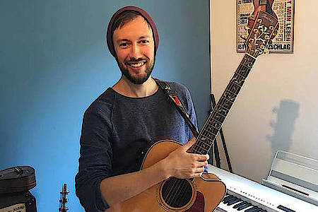 corby mit steht mit gitarre vor klavier