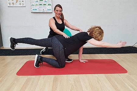 Frau macht Rückenübung
