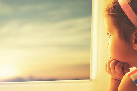 Kind schaut aus Fenster