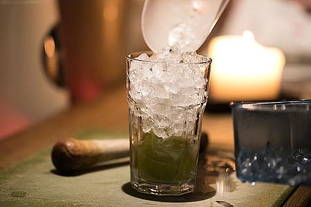 Eiswürfel werden in ein Cocktailglas gekippt