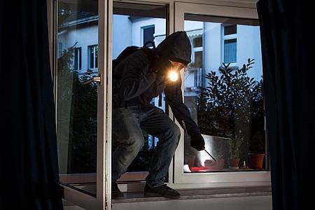 Einbrecher kommt durch ein Fenster