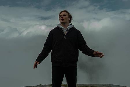 Mann vor dunklen Wolken