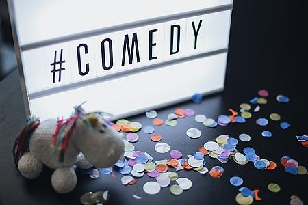 """Pummeleinhorn vor Lightbox mit der Schrift """"Comedy"""""""